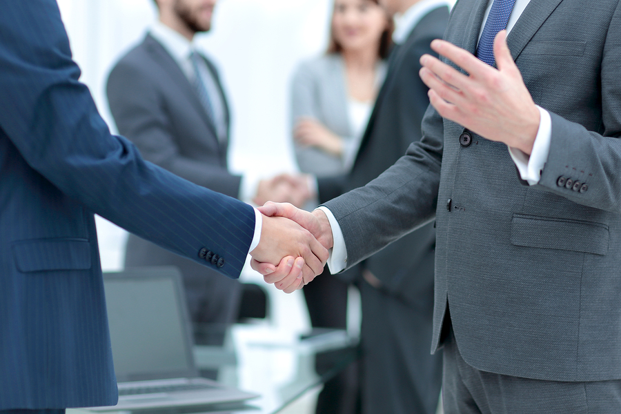 Businessmen in suits from 3PL companies shaking hands with other business people in the meeting room also greeting eachother in the background.