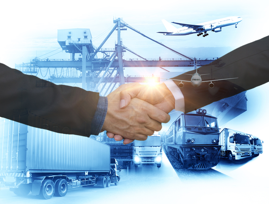 Logistics service providers shaking hands in front of a background of airlines, semi trucks and other logistics equipment.